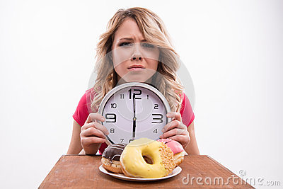 Time for diet slimming. Beautiful woman with clock