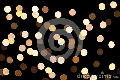Golden bokeh on a dark background. Defocused bokeh lignts. Abstract Christmas background. Abstract circular bokeh background of Ch