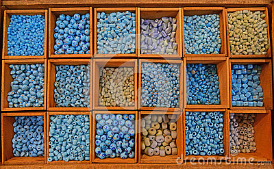 Colourful beads in different sizes and shapes sold in wooden compartment