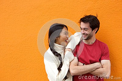 Two happy friends laughing against orange background
