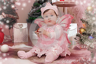 Baby girl with pink butterfly wings sitting under Christmas tree