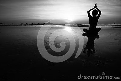 Young woman practicing yoga on the sea beach. Black and white high contrast photography.