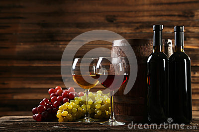 Glass of red and white wine with grapes on brown wooden background
