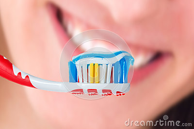 Red toothbrush with blue two color toothpaste on human smile