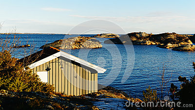 Small cottage fishing near  fjord