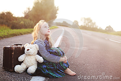 Orphan sits alone on the road