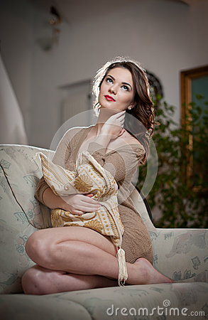 Young sensual woman sitting on sofa relaxing. Beautiful long hair girl with comfortable clothes daydreaming on the couch, alone