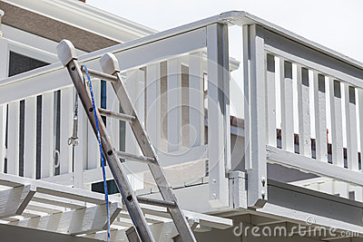 Construction Ladder and Painting Hose Leaning on House Deck