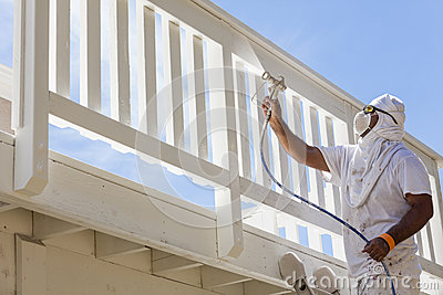 House Painter Spray Painting A Deck of A Home