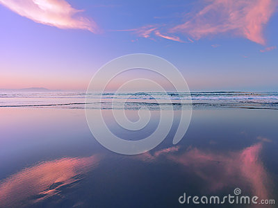 Sea at sunset with cloud reflections on sand