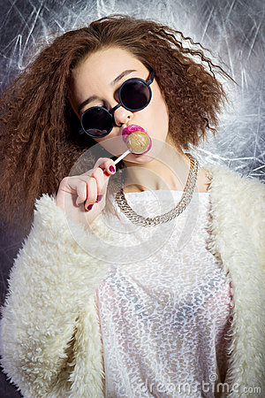 Funny beautiful girl in glasses and a white coat licks a candy bar, bright makeup, fashion photography Studio