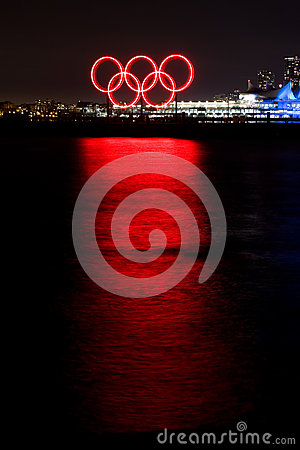 Red glowing Olympic rings reflected in the harbor