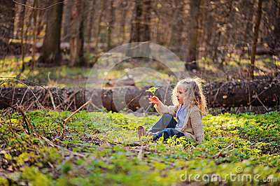 Cute child girl sitting in green leaves in early spring forest