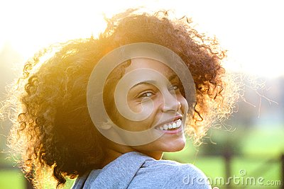 Cheerful young african american woman smiling outdoors