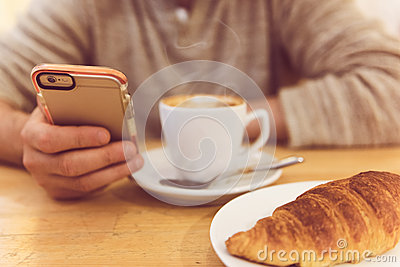 Detail image of unrecognisable man drinking coffee and holding smart phone while having breakfast in restaurant.