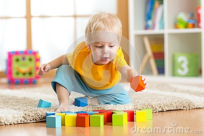Child toddler playing wooden toys at home