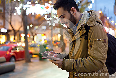 Portrait of young man using his mobile phone on the street at ni
