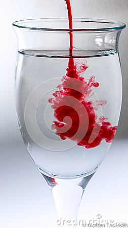 Red splash in glass of water.