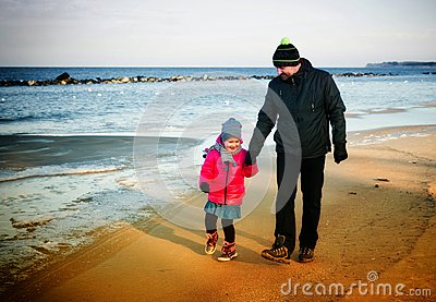 Father and daughter winter walk by the sea