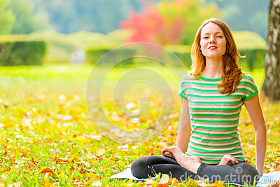 Barefoot red-haired girl practicing yoga in the park