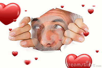 Composite image of man looking through torn paper