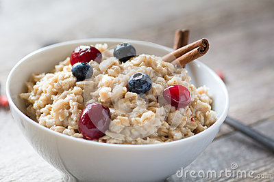 Breakfast oatmeal porridge with cinnamon, cranberries and blueberries