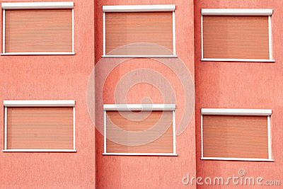 Red Building Facade with Six Closed Windows Shutters