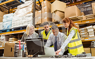 Warehouse managers and worker working on laptop