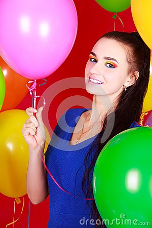 Nice young woman among many bright balloons