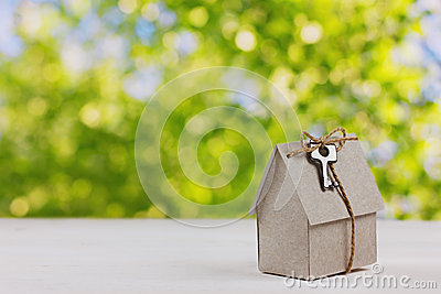 Model of cardboard house with a bow of twine and key against green bokeh background.