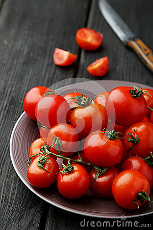 Fresh cherry tomatoes in plate on a black wooden background