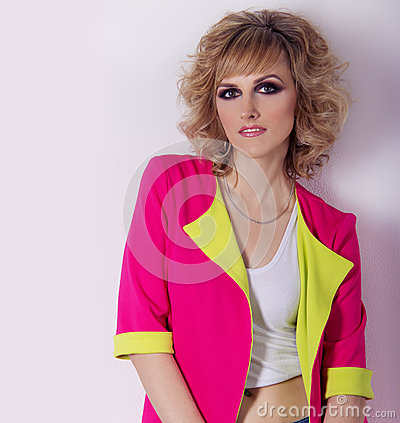 Beautiful young girl with bright eyes, sleek hair in a bright pink jacket, fashion photography Studio