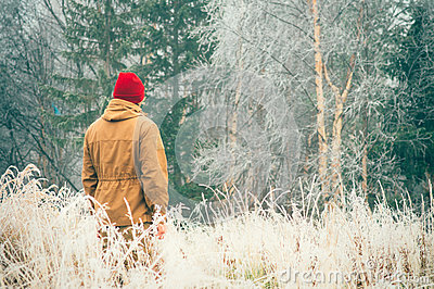 Young Man walking alone outdoor with foggy scandinavian forest nature on background