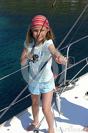 Girl fishing on a sailing yacht
