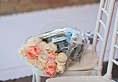 Gift rose bouquet in plastic wrapper on chair on wedding carpet