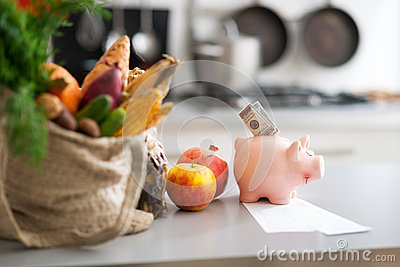 Closeup on money in piggy bank and purchases