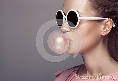 Beautiful blonde woman blowing bubble gum. Fashion portrait.