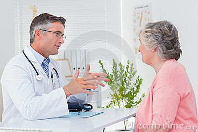 Male doctor conversing with female patient at table
