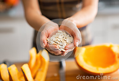 Closeup on young housewife showing pumpkin seeds