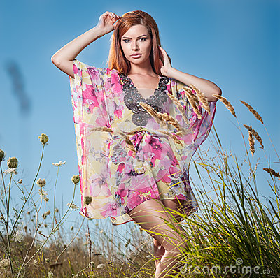 Beautiful young woman in wild flowers field on blue sky background. Portrait of attractive red hair girl with long hair relaxing