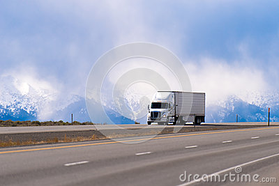 Spectacular white semi truck trailer reefer on highway in snow m