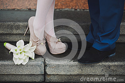 Young couple's legs. Woman and man in love. First date. Dating. Proposal. Lovers kissing. Beautiful calla lily flowers