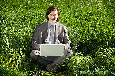 A business man with a laptop on the grass field