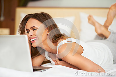 Beautiful young woman relaxing on her bed in white casual shirt using laptop