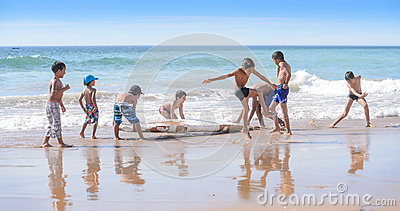 Kids playing with old surfboard, Taghazout surf village, agadir, morocco