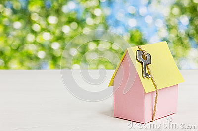 Model of cardboard house with a bow of twine and key against green bokeh background. house building, loan, real estate or buying