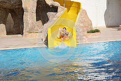 Young woman riding down a water slide-man enjoying a water tube ride