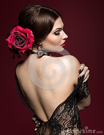 Young beautiful woman in black dress and black rose flower in ha