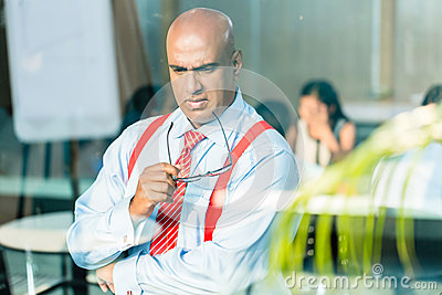 Indian Businessman thinking at office window
