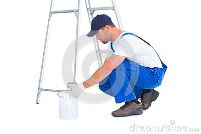 Side view of handyman with paint can on white background